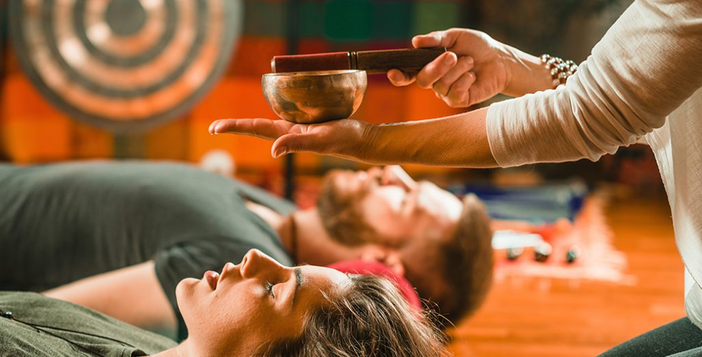 sound bathing sound bath tibetan singing bowl above two peoples heads yoga with priya
